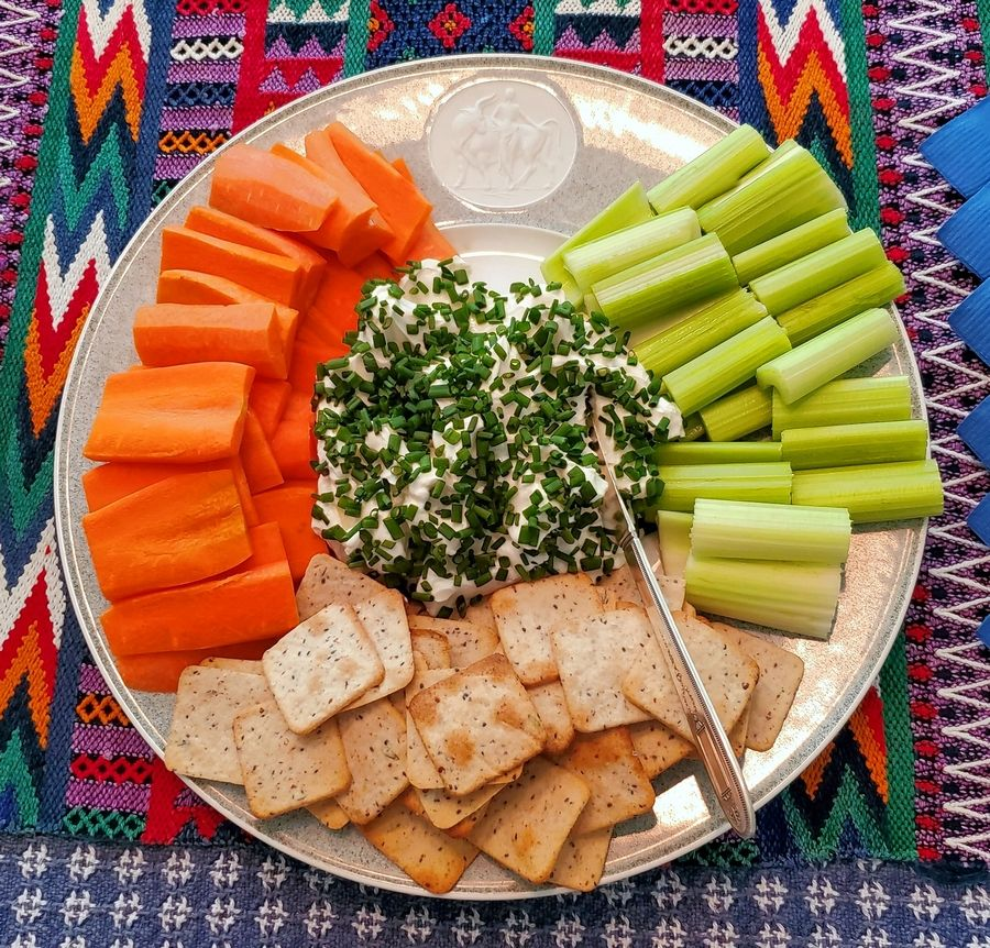 A dish of homemade labneh serves as an appetizer with fresh vegetables and crackers.