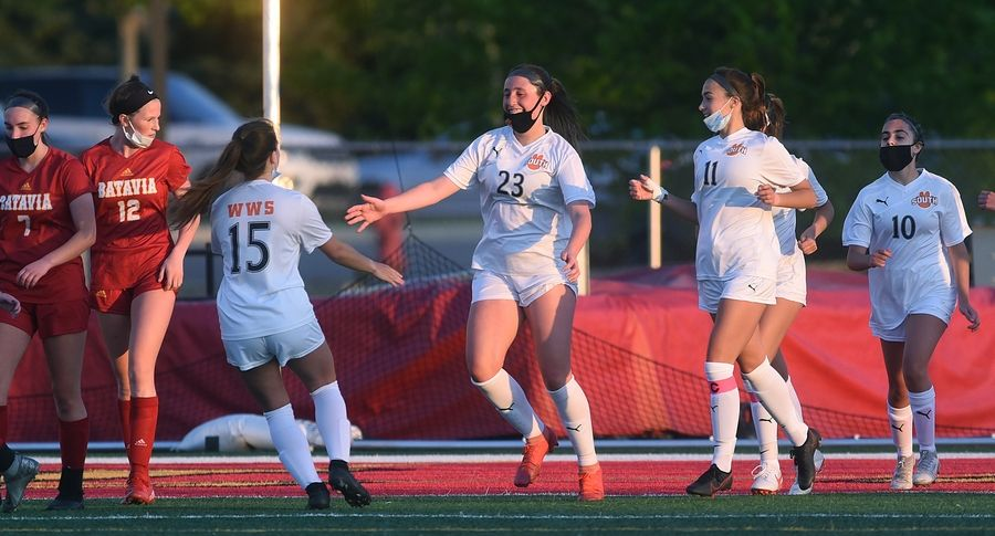 Wheaton Warrenville South's Lauren Barnett (23) gets a first-half goal and celebrates with teammates during Thursday's girls soccer game in Batavia.