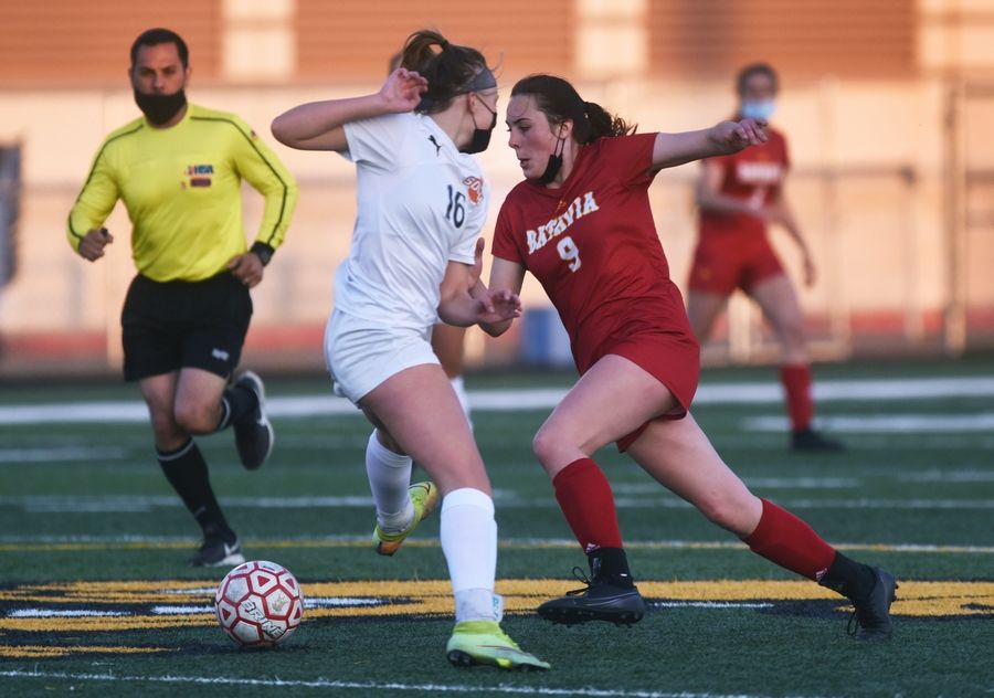 Batavia's Ashley Whelpley (9) guides the ball past Wheaton Warrenville South's Elise Farrell (16) during Thursday's girls soccer game in Batavia.