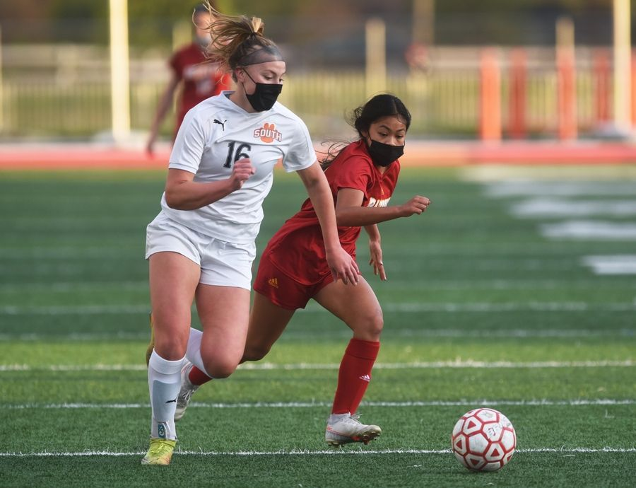 Wheaton Warrenville South's Elise Farrell (16) and Batavia's Laila Figueras chase the ball during Thursday's girls soccer game in Batavia.