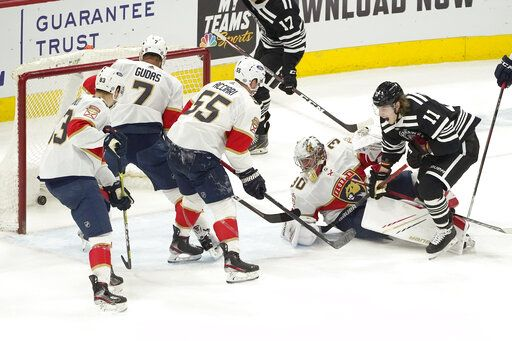 CORRECTS TO PANTHERS GOALTENDER SPENCER KNIGHT NOT PHILIPPE DESROSIERS - Chicago Blackhawks' Adam Gaudette (11) scores past Florida Panthers goaltender Spencer Knight (30) during the first period of an NHL hockey game Thursday, April 29, 2021, in Chicago.