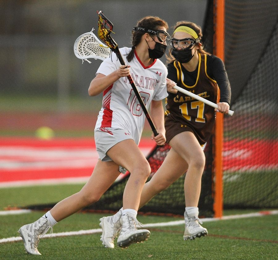 Carmel's Mary Powers sticks to Palatine's Jane Spencer in a girls lacrosse game in Palatine Friday.