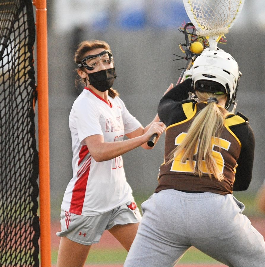 Palatine's Jane Spencer tries to sneak the ball into the net guarded by Carmel goalkeeper Megan Bauer in a girls lacrosse game in Palatine Friday, April 30, 2021.