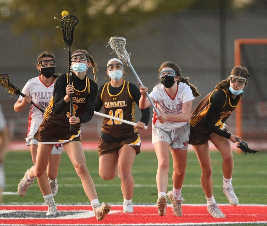 Carmel's Reagan Dinner comes up with a loose ball against Palatine in a girls lacrosse game in Palatine Friday, April 30, 2021.