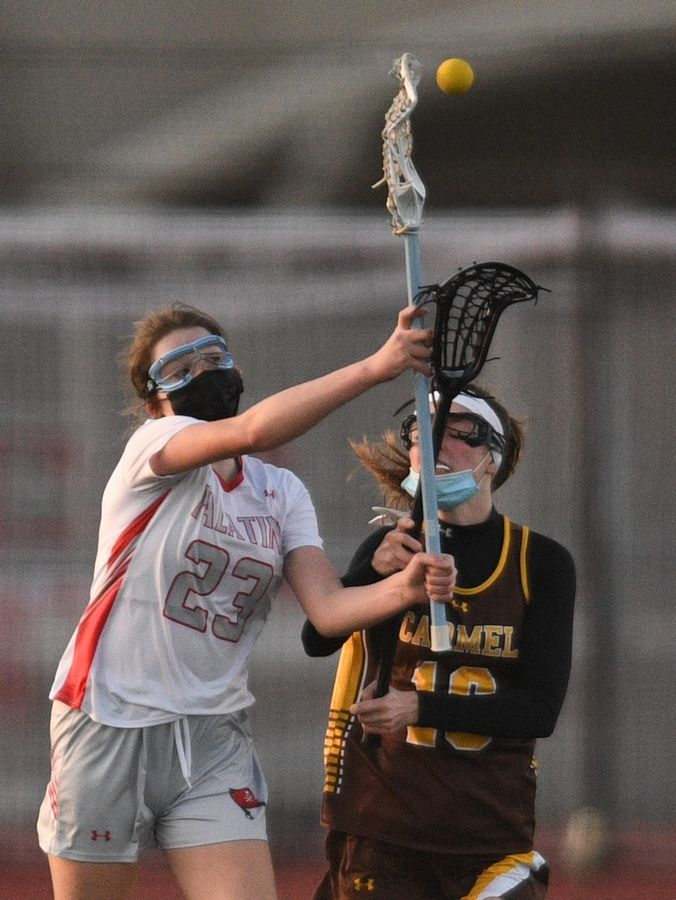 Palatine's Ashley Roe passes to a teammate as Carmel's Megan Spanswick chases her in a girls lacrosse game in Palatine Friday, April 30, 2021.