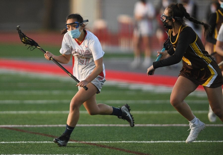 Palatine's Megan Kim is chased by Carmel's Lainey Cordova in a girls lacrosse game in Palatine Friday, April 30, 2021.