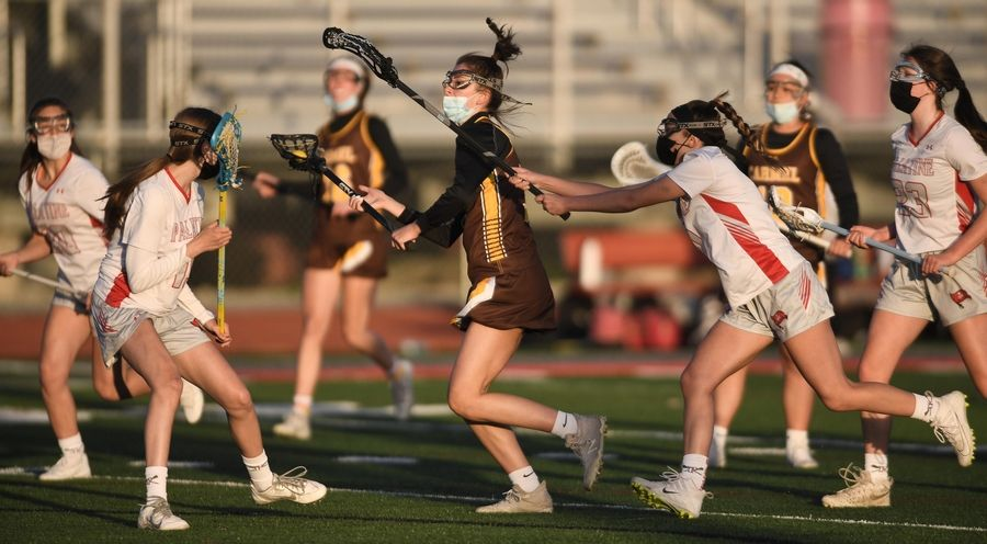 Carmel's Reagan Dinner is harassed by Palatine's Zeny Hughes in a girls lacrosse game in Palatine Friday, April 30, 2021.