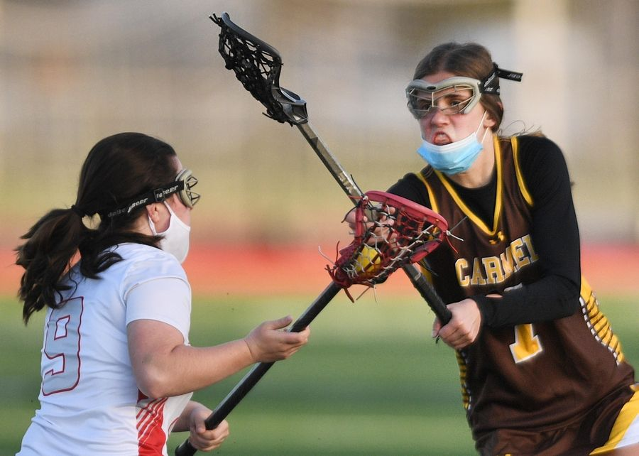 Carmel's Mara Geier defends Palatine's Callie O'Connell in a girls lacrosse game in Palatine Friday, April 30, 2021.