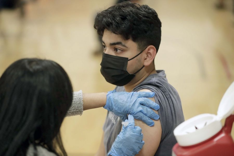 Rene Sarmiento, 17, of Lombard, a student at Glenbard West High School, gets a Pfizer COVID-19 shot Friday at the Sports Hub in Glendale Heights. Several suburban school districts are working to get students vaccinated voluntarily before this school year ends.