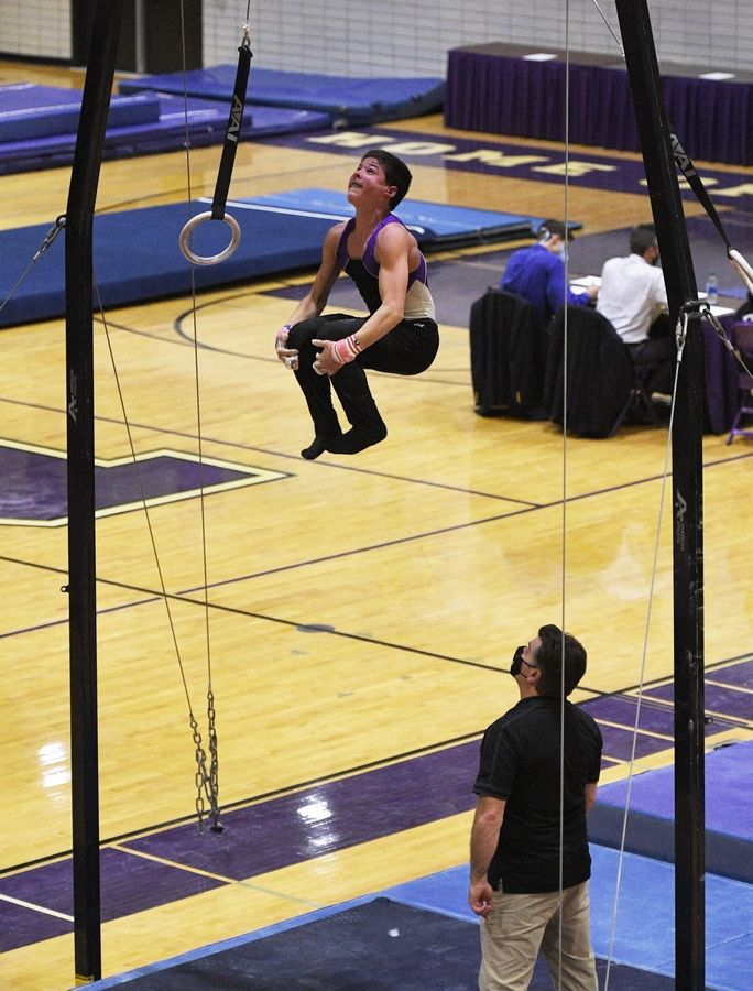 Downers Grove North's Anthony Nicholas dismounts the Still Rings at the boys gymnastics sectional meet at Downers Grove North High School Monday.