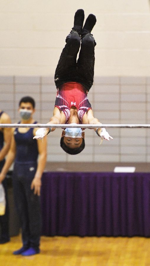 Glenbard East's Vader Srey on the High Bar at the boys gymnastics sectional meet at Downers Grove North High School Monday, May 3, 2021.