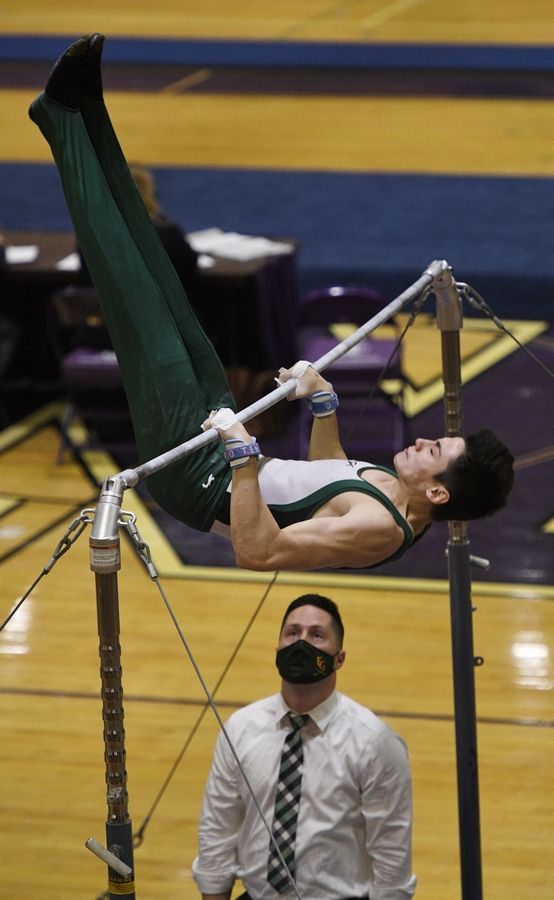 Elk Grove's Flynn Behnke on the High Bar at the boys gymnastics sectional meet at Downers Grove North High School Monday, May 3, 2021.