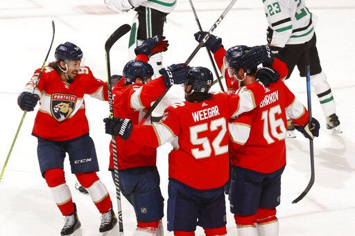 Teammates celebrate the game-winning goal by Florida Panthers center Aleksander Barkov (16) during the overtime period of an NHL hockey game, Monday, May 3, 2021, in Sunrise, Fla.