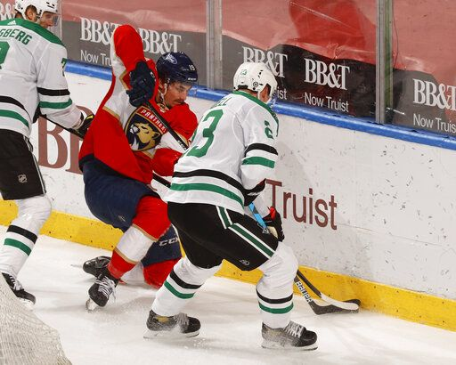 Florida Panthers left wing Mason Marchment (19) and Dallas Stars defenseman Esa Lindell (23) battle for control of the puck during the second period of an NHL hockey game, Monday, May 3, 2021, in Sunrise, Fla.