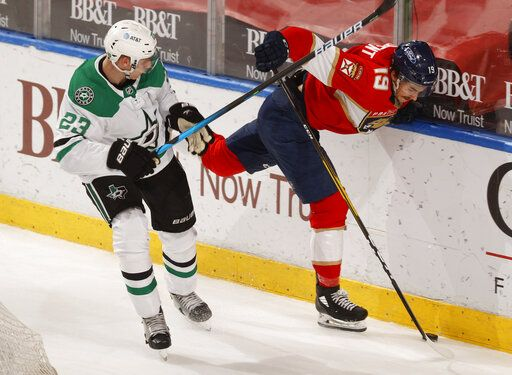Dallas Stars defenseman Esa Lindell (23) checks Florida Panthers left wing Mason Marchment (19) off the puck during the second period of an NHL hockey game, Monday, May 3, 2021, in Sunrise, Fla.