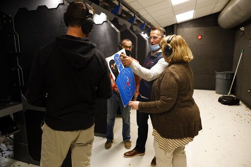 Chicago resident Ray Mandel, center, shows his target to others during a shooting session at Maxon Shooter's Supplies and Indoor Range, Friday, April 30, 2021, in Des Plaines, Ill. After a year of pandemic lockdowns, mass shootings are back, but the guns never went away. As the U.S. inches toward a post-pandemic future, guns are arguably more present in the American psyche and more deeply embedded in American discourse than ever before. The past year's anxiety and loss fueled a rise in gun ownership across political and socio-economic lines.