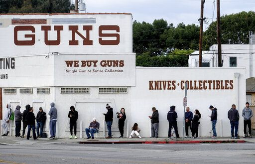 FILE - In this Sunday, March 15, 2020, file photo, people wait in line to enter a gun store in Culver City, Calif. After a year of pandemic lockdowns, mass shootings are back, but the guns never went away. As the U.S. inches toward a post-pandemic future, guns are arguably more present in the American psyche and more deeply embedded in American discourse than ever before. The past year's anxiety and loss fueled a rise in gun ownership across political and socio-economic lines.