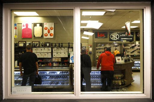 Customers stand inside the gun shop area of Maxon Shooter's Supplies and Indoor Range, as seen from the shooting range, Friday, April 30, 2021, in Des Plaines, Ill. After a year of pandemic lockdowns, mass shootings are back, but the guns never went away. As the U.S. inches toward a post-pandemic future, guns are arguably more present in the American psyche and more deeply embedded in American discourse than ever before. The past year's anxiety and loss fueled a rise in gun ownership across political and socio-economic lines.