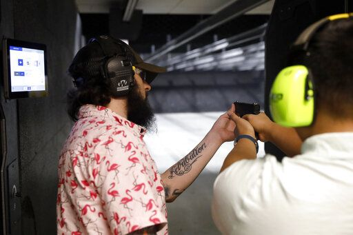 Firearms trainer Kevin Burke, left, instructs new gun owner Troy Deguzman during a shooting session at Maxon Shooter's Supplies and Indoor Range, Friday, April 30, 2021, in Des Plaines, Ill. After a year of pandemic lockdowns, mass shootings are back, but the guns never went away. As the U.S. inches toward a post-pandemic future, guns are arguably more present in the American psyche and more deeply embedded in American discourse than ever before. The past year's anxiety and loss fueled a rise in gun ownership across political and socio-economic lines.