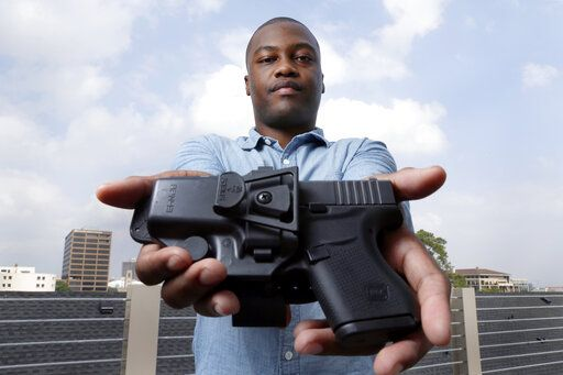 "Charles Blain, a new gun owner, poses with his holstered 9mm Glock 43 handgun, Monday, May 3, 2021, on the parking garage of his apartment complex in Houston. Blain also owns a shotgun and is currently completing his concealed carry license requirements to carry the handgun. Blain, who describes himself as a conservative, says ""pandemic-related unemployment crime"" and repeated calls over the past year to release hundreds of jail inmates because of soaring COVID-19 infections pushed him to buy."
