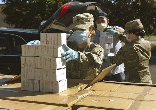 FILE - In this Wednesday, May 27, 2020, file photo, Oregon National Guard's Ashley Smallwood, of Springfield, Ore., counts out boxes of face masks to be given to Willamette Valley farmers while participating in a distribution event at the Oregon State University Extension Service-Linn County office in Tangent, Ore. Oregon adopted a controversial rule on Tuesday, May 4, 2021 that indefinitely extends coronavirus mask and social distancing requirements in all businesses in the state. State officials say the rule, which garnered thousands of public comments, will be in place until it is 'œno longer necessary to address the effects of the pandemic in the workplace.'� (Mark Ylen/Albany Democrat-Herald via AP, file)