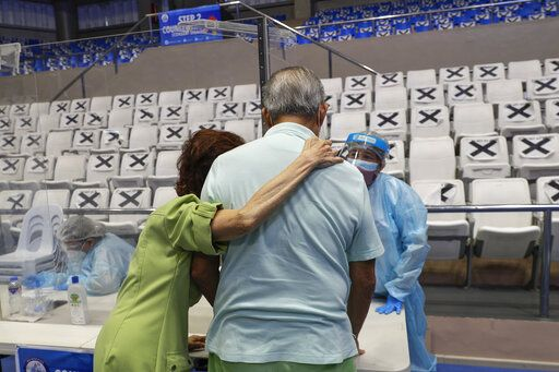 An elderly couple talks to a health worker at a vaccination center inside the Makati Coliseum in Manila, Philippines on Tuesday, May 4, 2021. The Philippines started a simultaneous vaccination of the initial 15,000 doses of Russia's Sputnik V COVID-19 vaccines that arrived in the country earlier this week.