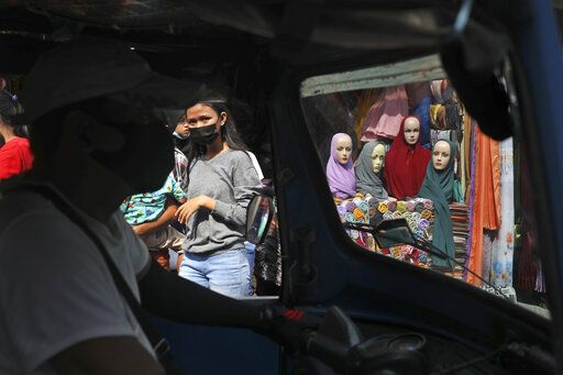 "Mannequins and women wearing masks to curb the spread of coronavirus outbreak are seen through the windows of a three-wheeled motorized taxi called ""bajaj"", during the last week of Ramadan at a market in Jakarta, Indonesia, Tuesday, May 4, 2021. People flock markets and shopping malls in the capital as they shop for food and new clothings in preparation for Eid al Fitr holiday that marks the end of the holiest month in Islamic calendar."