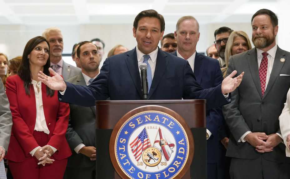 Surrounded by lawmakers, Florida Gov. Ron DeSantis speaks Friday at the end of a legislative session at the Capitol in Tallahassee, Florida.
