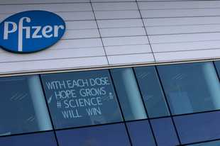 In this Tuesday, Feb. 23, 2021 file photo, a sign is pasted into an upper window at Pfizer manufacturing center in Puurs, Belgium.