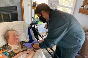 Naperville paramedic Jason Rothenberg administers a Johnson & Johnson COVID-19 shot to Marsha Slaboch, who has multiple sclerosis and is homebound.