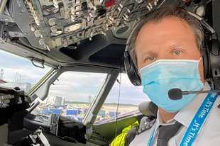 American Airlines pilot Dennis Tajer wears a mask as required by a federal rule instituted Jan. 21.