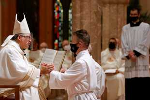 Johnny Burnett kneels before Bishop Robert Casey and promises his respect and obedience during the Rite of Ordination Saturday at Holy Name Cathedral in Chicago. Burnett, of Mount Prospect, was among 22 Catholic deacons ordained on Saturday.