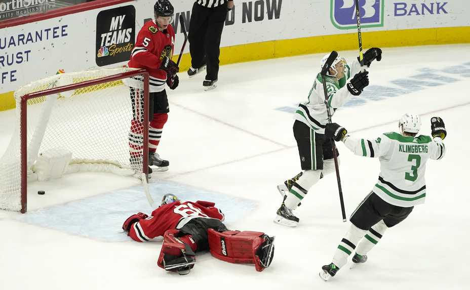 Dallas Stars' Jason Robertson (21) celebrates his winning goal with John Klingberg (3) as Chicago Blackhawks goaltender Collin Delia and Connor Murphy (5) look on during the overtime period of an NHL hockey game Monday, May 10, 2021, in Chicago.