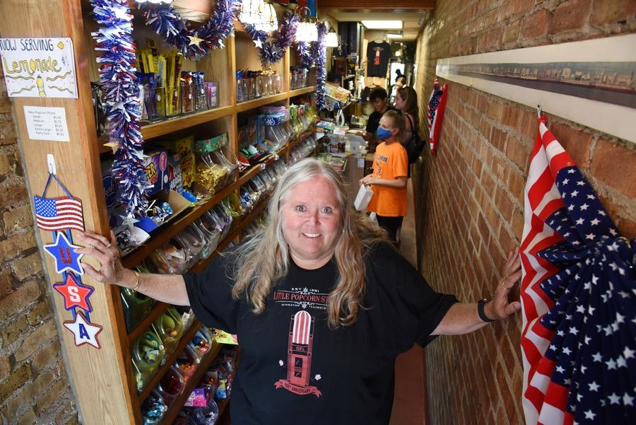 Donna Wakefield can touch both interior walls of her Little Popcorn Store in downtown Wheaton. The store is celebrating its 100th anniversary this weekend.