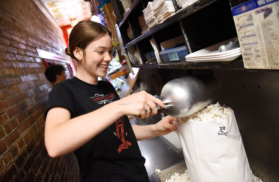 Sadie Chelsen bags popcorn Thursday at the Little Popcorn Store in downtown Wheaton. The store is celebrating its centennial this weekend.
