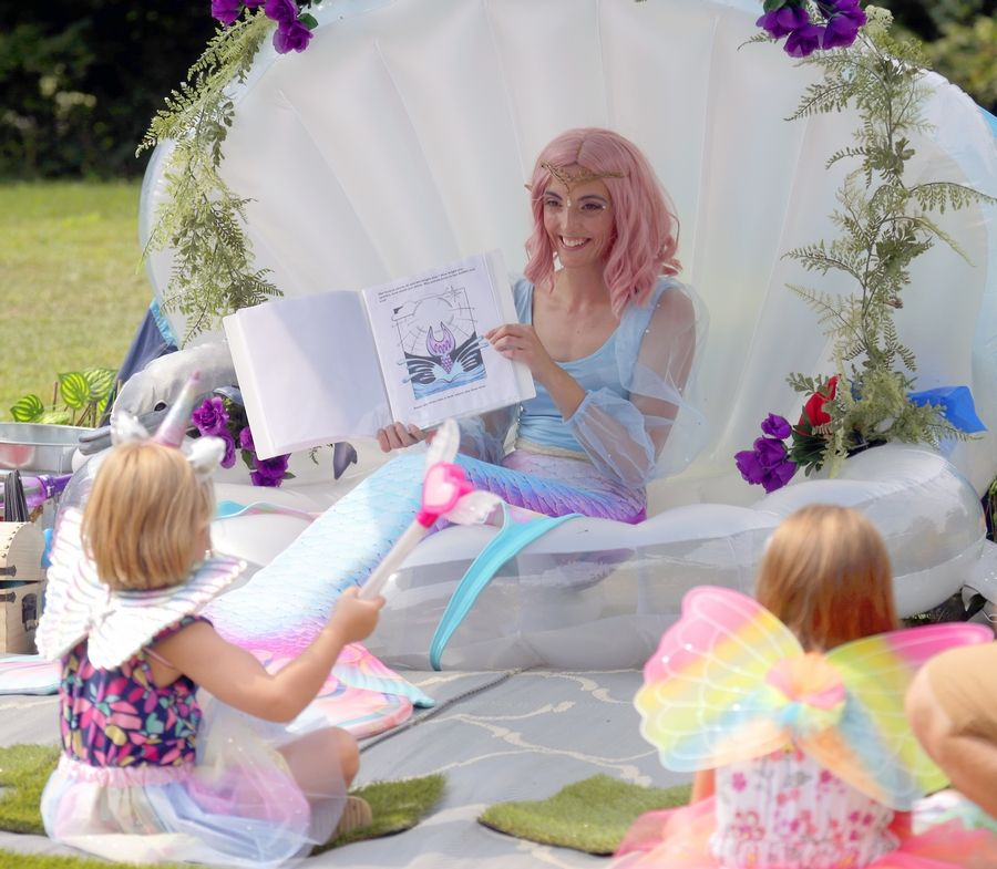 """Alanna """"Merbubbles"""" Turner of Chicago Ridge reads to children during the World of Faeries Festival Saturday in South Elgin."""