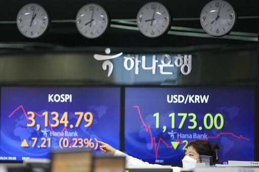 A currency trader passes by screens showing the Korea Composite Stock Price Index (KOSPI), left, and the exchange rate of South Korean won against the U.S. dollar at the foreign exchange dealing room of the KEB Hana Bank headquarters in Seoul, South Korea, Thursday, Sept. 23, 2021. Asian shares were mostly higher on Thursday after the Federal Reserve signaled it may begin easing its extraordinary support measures for the economy later this year.