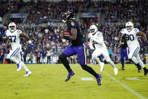 Baltimore Ravens quarterback Lamar Jackson (8) scrambles away from Indianapolis Colts defenders during the first half of an NFL football game, Monday, Oct. 11, 2021, in Baltimore.