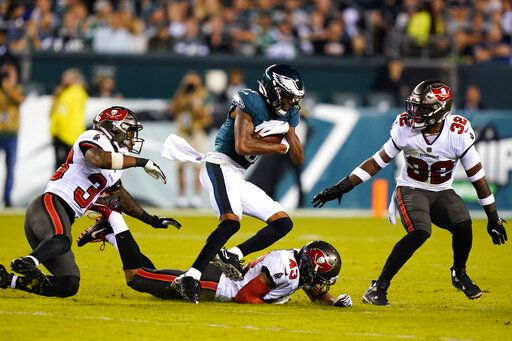 Philadelphia Eagles long setter DeVonta Smith (6) runs the ball past Tampa Bay Buccaneers Ross Cockrell, bottom, Mike Edwards, right, and Jordan Whitehead in the second half of the NFL football game on Thursday, October 14, 2021, in Philadelphia.