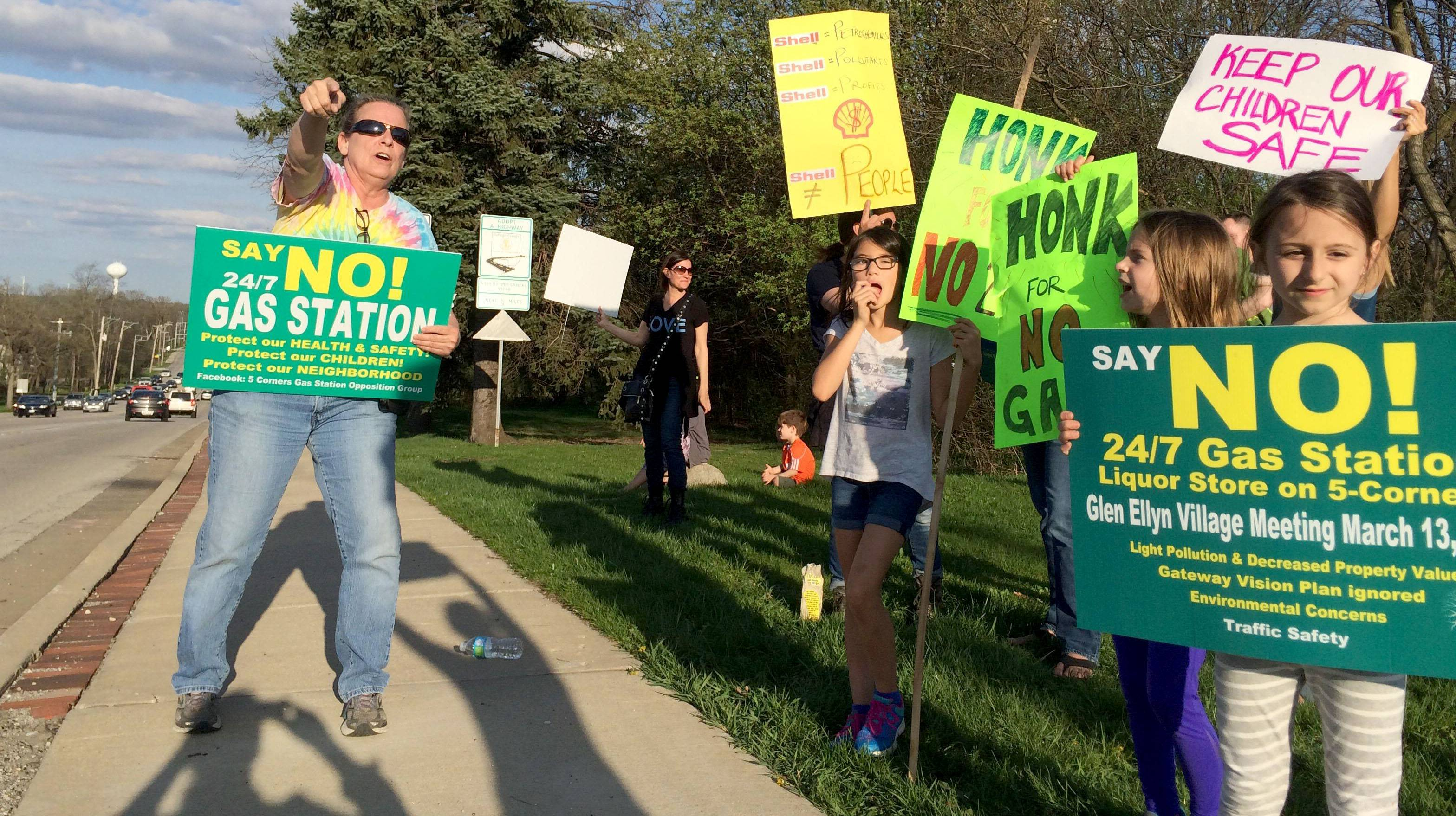 Mary Beth Nelms, left, joined a protest against plans for a gas station at the southeast corner of Main Street and St. Charles Road in Glen Ellyn.