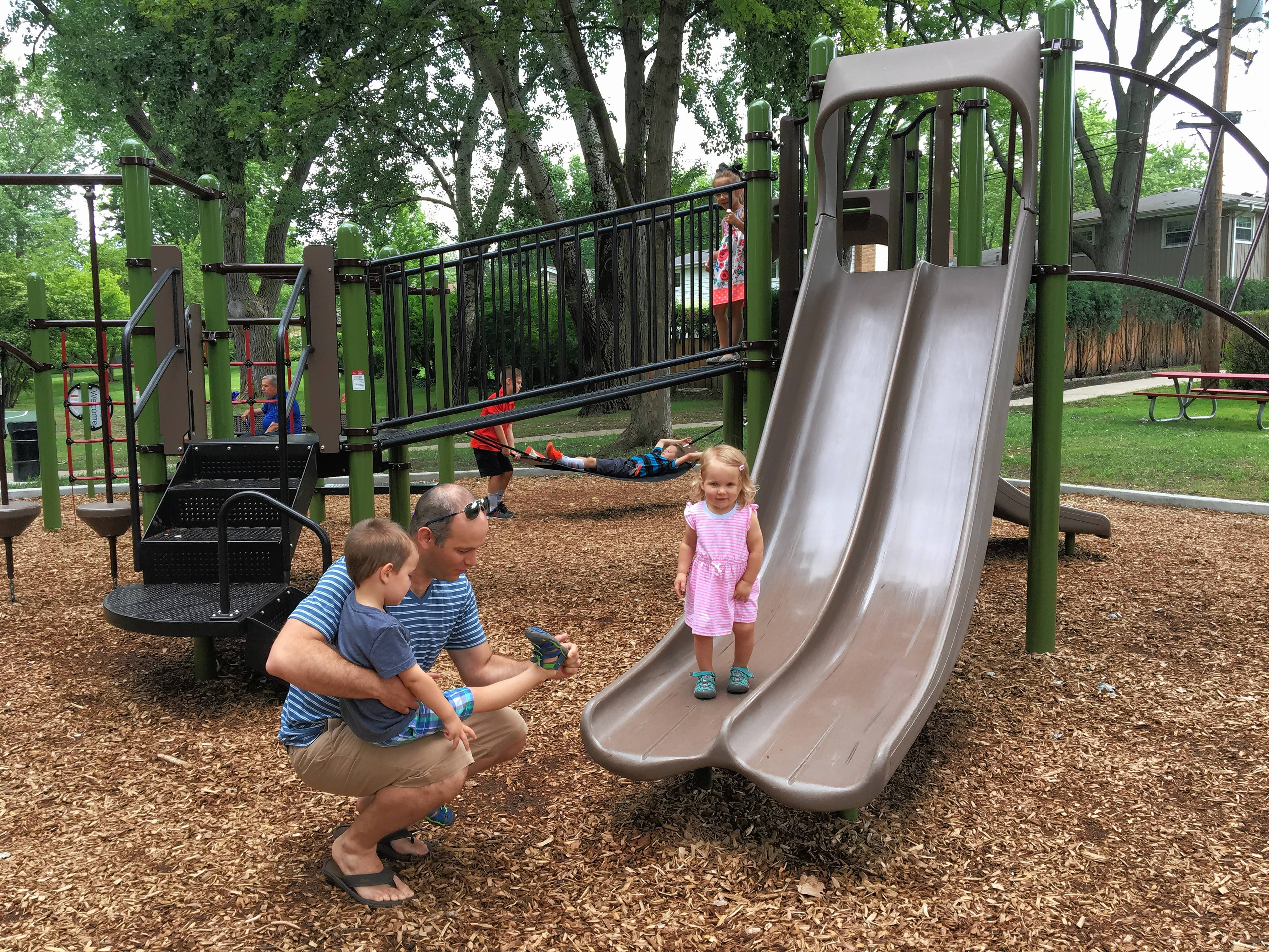 Alan Deitch helps take shoes off his son, Wesley, 3, as daughter, Elenor, 18 months, stands on a slide that is part of new playground equipment at We-Go Park Play Lot in Mount Prospect.