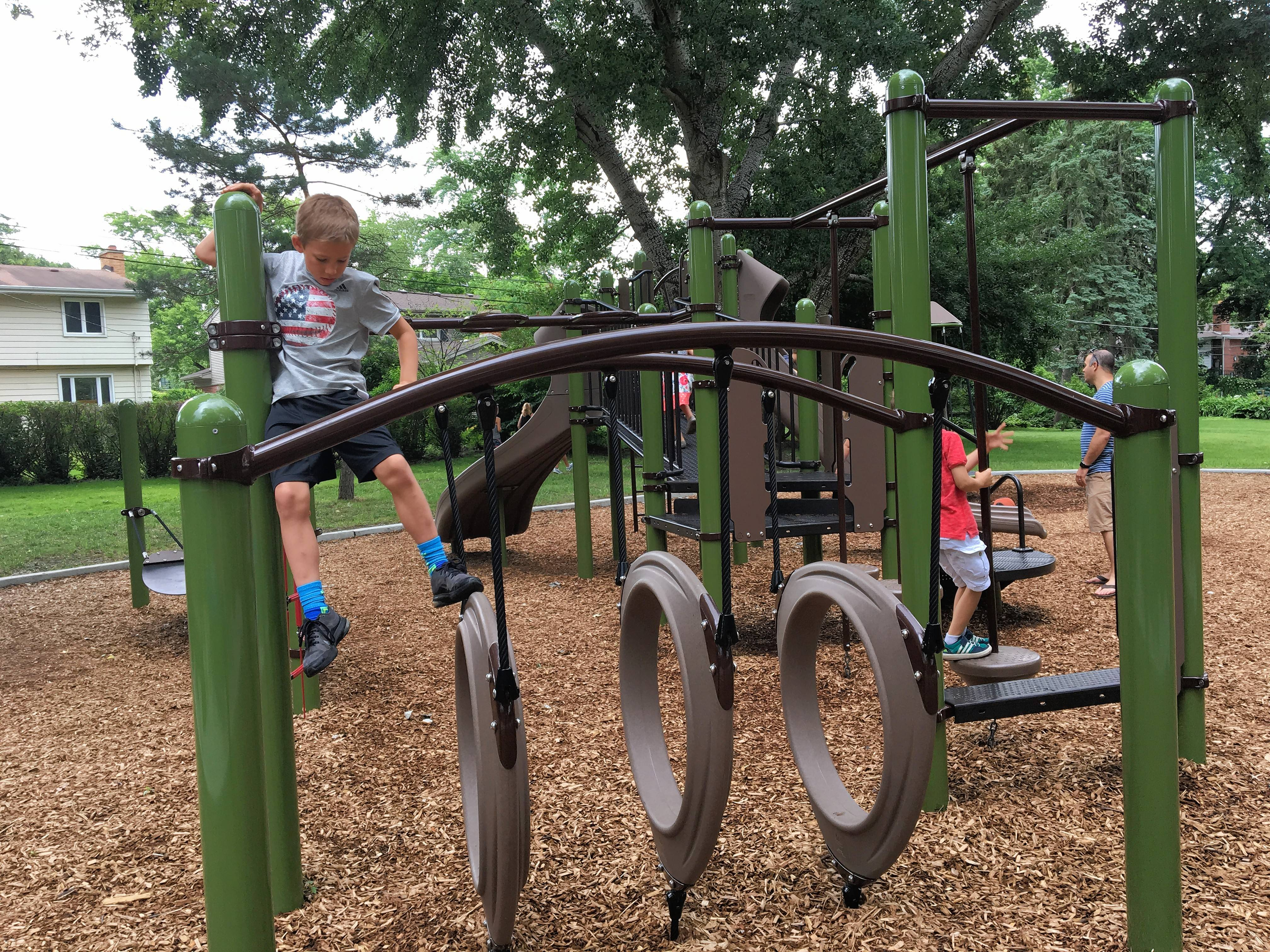 "Gordon Kemp, 8, plays on new playground equipment in his neighborhood park, We-Go Park Play Lot, which was upgraded last year and dedicated Saturday by the Mount Prospect Park District. ""It's a lot better than it was before,"" he said."