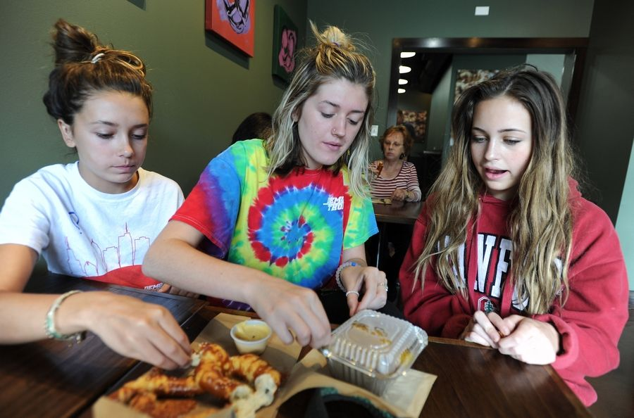 Brooke Cullen, 13, and her sister Sarah, 18, with Mia Carroll, 13, all of Barrington, enjoy Tuesday's opening of Gnarly Knots Pretzel Co. in the village's downtown on Hough Street.