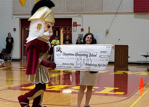 Michele Napier, chairwoman of the student services department at Schaumburg High School, displays a check for $2,000, which the students raised during their homecoming week to donate to Cimarron Elementary School in Katy, Texas.