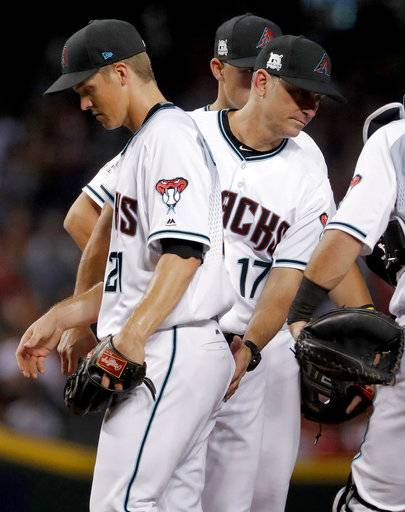 Arizona Diamondbacks starting pitcher Zack Greinke (21) is removed by manager Torey Lovullo (17) during the fourth inning of the National League wild-card playoff baseball game against the Colorado Rockies, Wednesday, Oct. 4, 2017, in Phoenix.