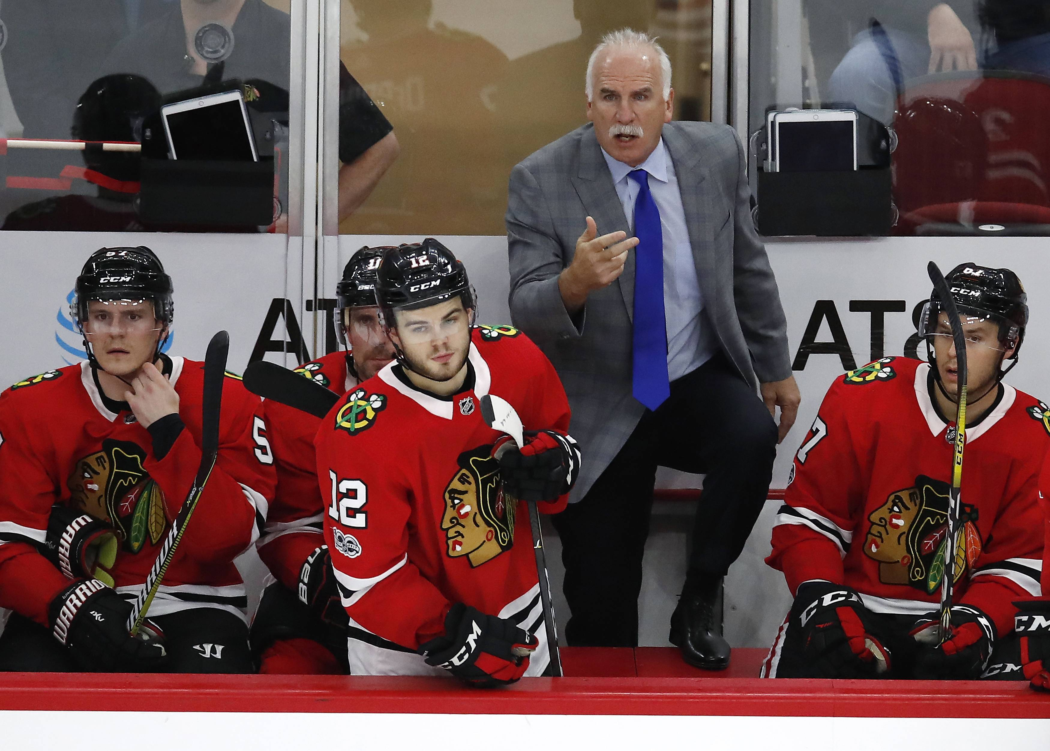 After his challenge was dismissed, Chicago Blackhawks coach Joel Quenneville tries to call over an official during the third period of the team's game against the Minnesota Wild on Thursday in Chicago.