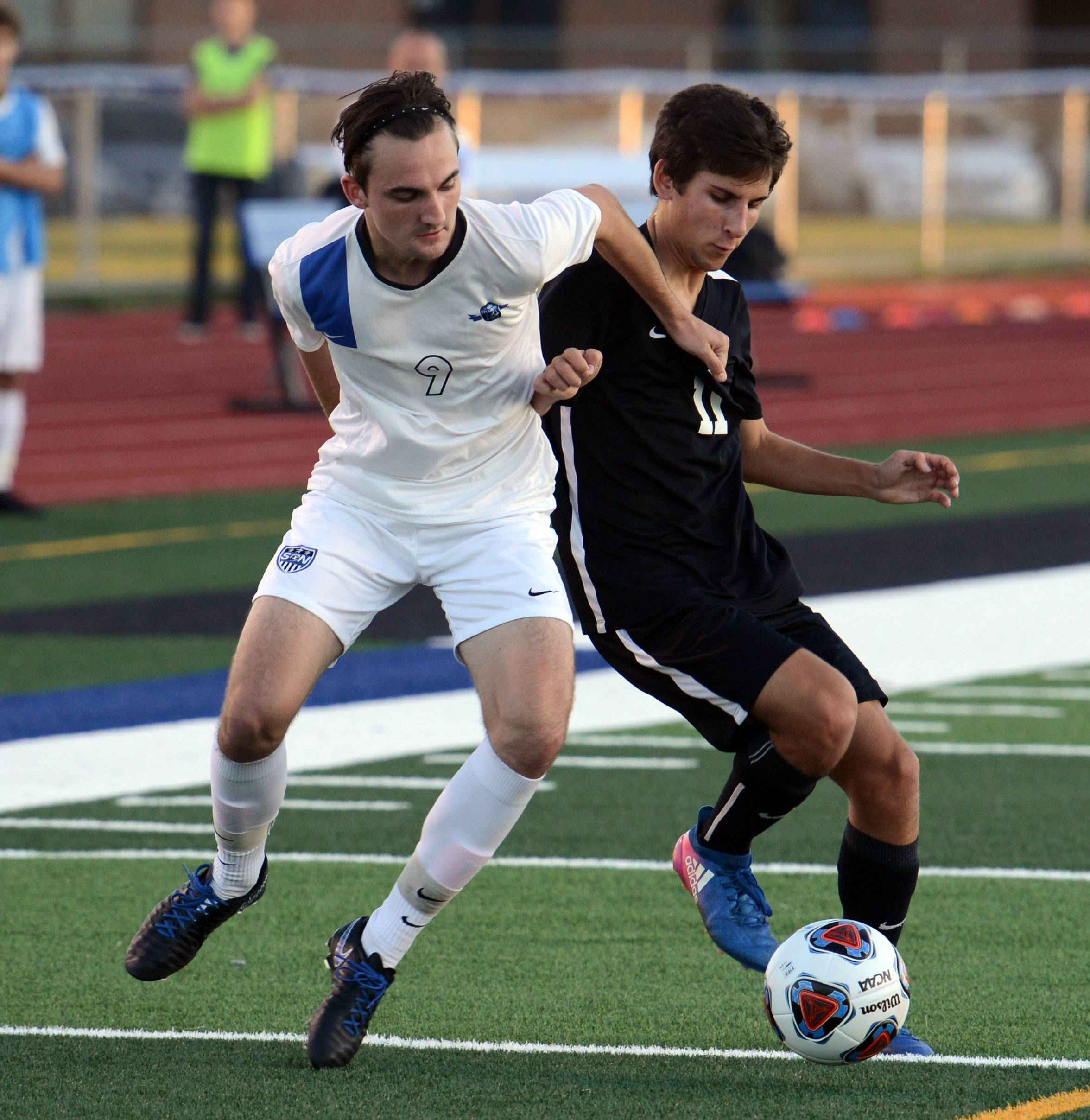 St. Charles North's Jake Persenico (9) battles Willowbrook's David Rizzo (11) for the ball during regional action at St. Charles North Tuesday.