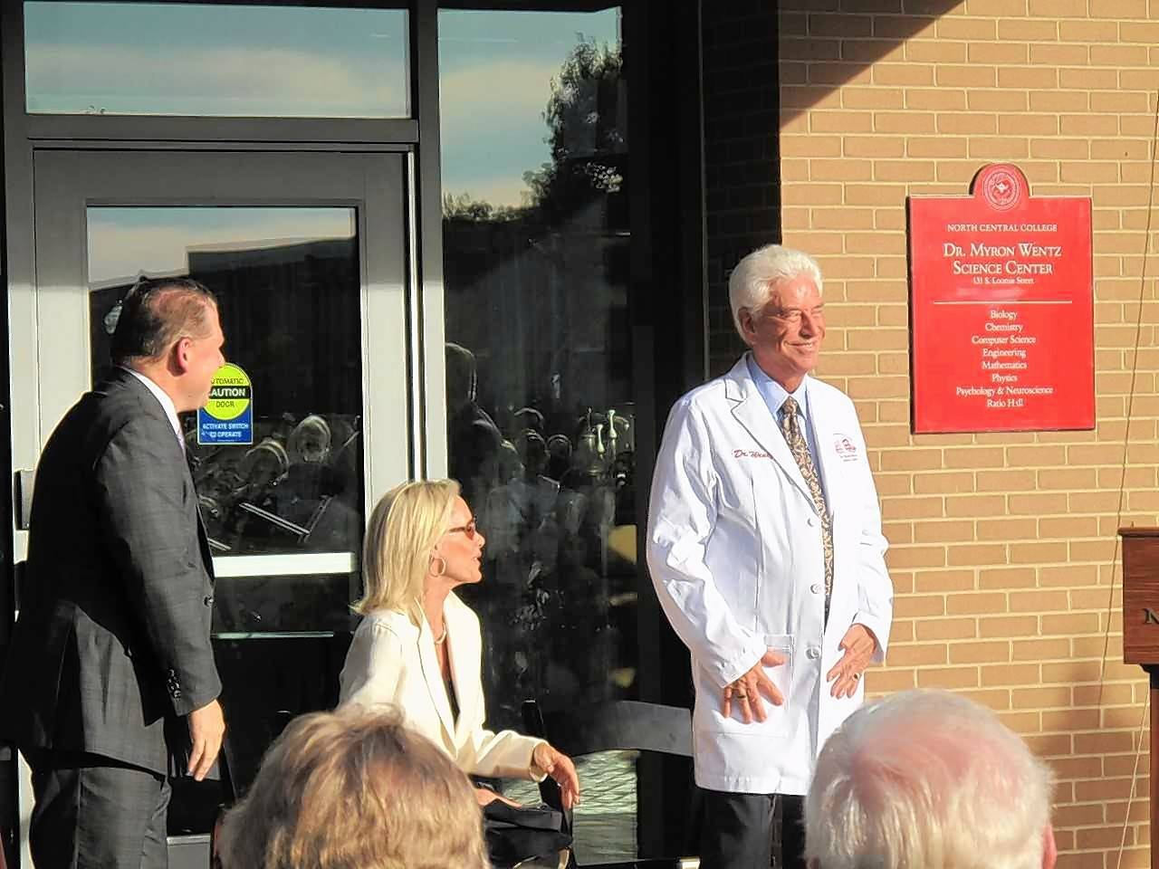 Scientist and North Central College alum Myron Wentz dons a special lab coat the college's science faculty gave him Friday as officials dedicated the college's $60 million science center in his name.
