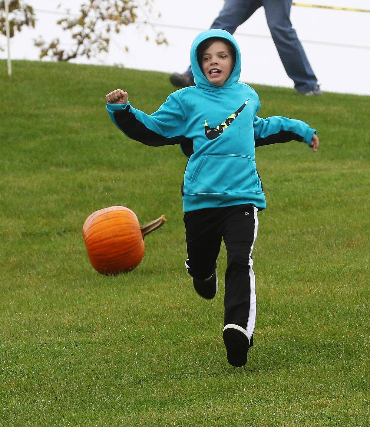 Michael Pacella, 8, of Mundelein is chased by the pumpkin that he started rolling down the sled hill at the Mundelein Community Center on Sunday. The traditional pumpkin roll and pumpkin catapult were canceled due to weather but kids took them up the sled hill on their own.