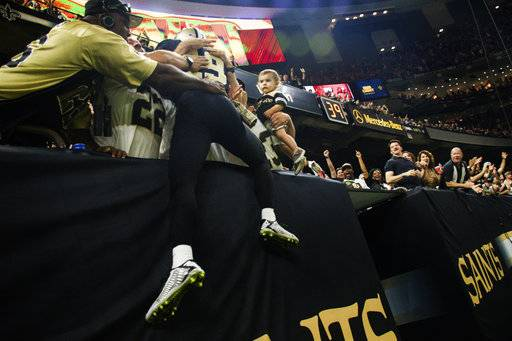 Saints wide receiver Ted Ginn Jr leaps into the stands after catching a Drew Brees pass for a touchdown as The New Orleans Saints take on The Tampa Bay Buccaneers in an NFL football game Sunday, Nov. 5, 2017 in Lafayette, La. (Scott Clause/The Daily Advertiser via AP)